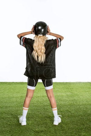rear view of woman in american football uniform standing on grass isolated on white