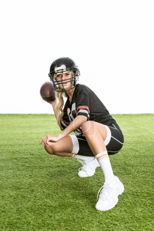 sporty young woman in american football uniform throwing ball while sitting squats on grass isolated on white