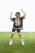 young woman in american football uniform celebrating victory while standing on grass isolated on white