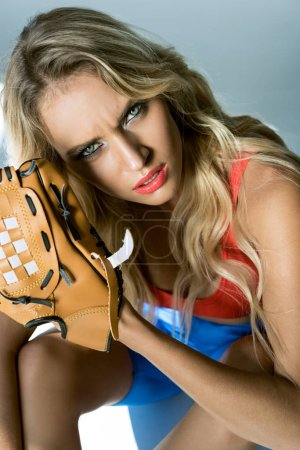 close-up portrait of young woman with baseball glove looking at camera