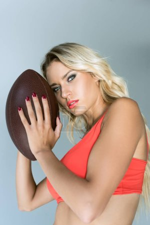 close-up portrait of sporty young woman holding american football ball and looking at camera on grey