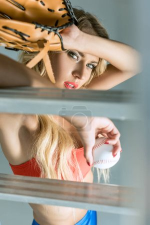 attractive young woman leaning on stepladder with baseball glove and ball