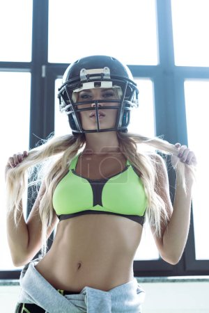 fit young woman in sport bra and american football helmet looking at camera