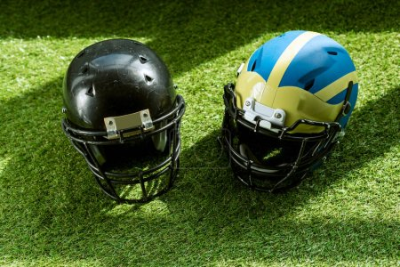 high angle view of american football safety helmets on green grass