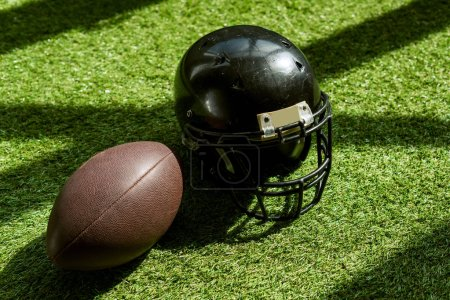 high angle view of american football ball and helmet on green grass