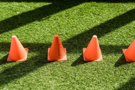 high angle view of row of safety cones standing on grass field