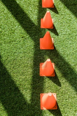 high angle view of row of safety cones standing on green grass