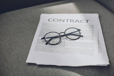 eyeglasses and business contract on grey armchair in office