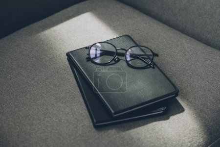 Photo for Eyeglasses and two notebooks on grey armchair in office - Royalty Free Image