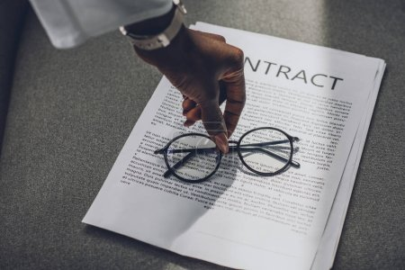 cropped image of african american businesswoman putting glasses on contract in office