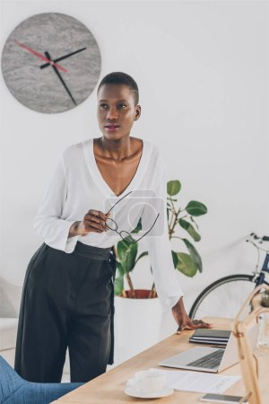 fashionable attractive african american businesswoman holding glasses and leaning on table in office