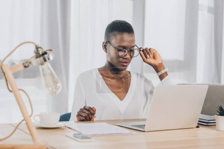 stylish attractive african american businesswoman touching glasses and looking at laptop in office