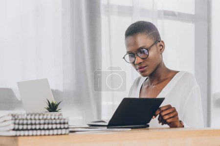 stylish attractive african american businesswoman looking in open notebook in office