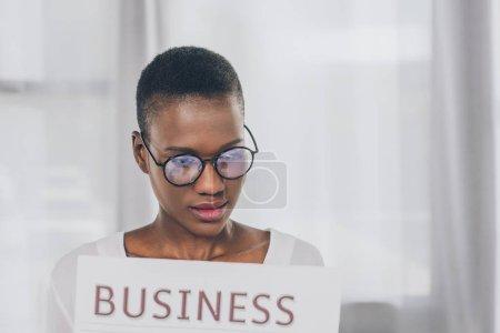 Photo pour Portrait de femme d'affaires afro-américains dans des verres de lecture de journal au bureau - image libre de droit