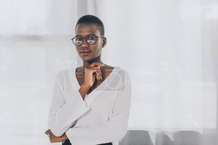 pensive stylish african american businesswoman looking at camera in office