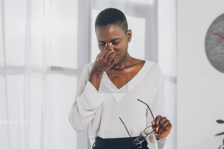 tired stylish african american businesswoman touching nose bridge and holding glasses in office