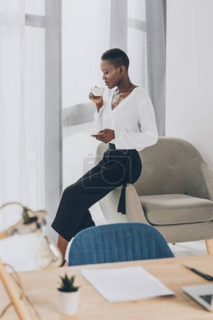 side view of stylish african american businesswoman sitting on armchair and drinking coffee in office