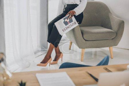 Photo pour Image recadrée d'une femme d'affaires afro-américaine assise sur un fauteuil et tenant un journal en fonction - image libre de droit