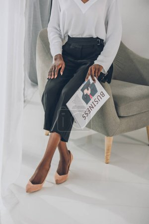 cropped image of stylish african american businesswoman sitting on armchair and holding newspaper in office