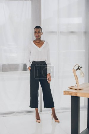 fashionable attractive african american businesswoman looking at camera in office