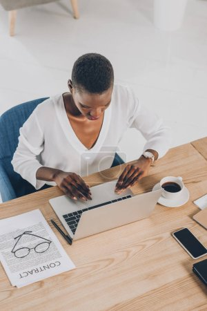 high angle view of stylish attractive african american businesswoman using laptop in office