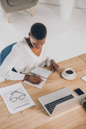 high angle view of stylish african american businesswoman writing to notebook in office