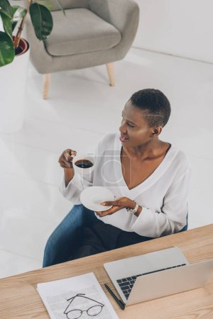 high angle view of stylish attractive african american businesswoman holding cup of coffee in office