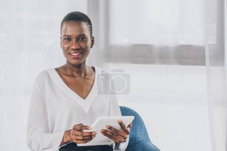 Photo pour Sourire élégante attrayante femme afro-américaine tenant la tablette au bureau - image libre de droit