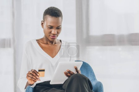 beautiful african american businesswoman shopping online with tablet and credit card in office