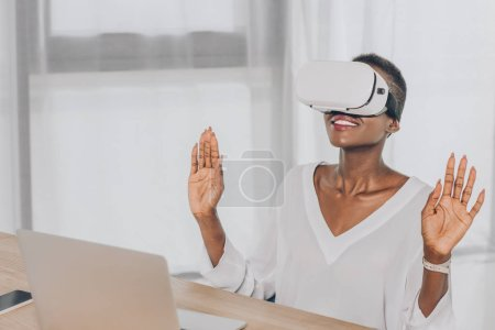 stylish surprised african american businesswoman looking up in virtual reality headset in office