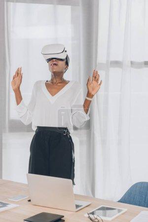 Foto de Elegante empresaria afroamericana sorprendida mirando hacia arriba en el casco de realidad virtual en la oficina - Imagen libre de derechos