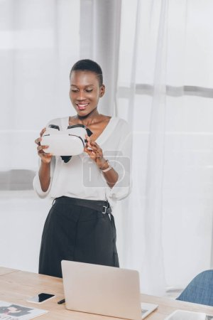 smiling stylish african american businesswoman holding virtual reality headset in office