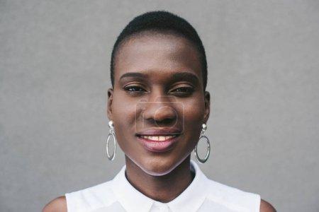 Photo pour Portrait de souriant élégant attrayant afro-américain femme regardant la caméra près du mur gris - image libre de droit