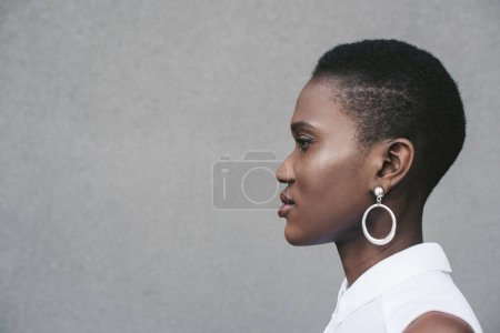 side view of stylish attractive african american woman standing near grey wall