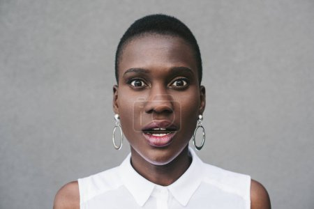 portrait of surprised stylish attractive african american woman looking at camera near grey wall