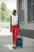 fashionable attractive african american businesswoman walking with travel bag on street