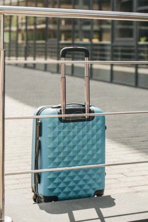 Photo for Light blue travel bag near railing on street - Royalty Free Image