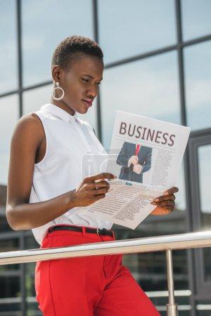 stylish beautiful african american businesswoman reading newspaper near business center