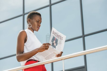 low angle view of stylish african american businesswoman reading newspaper near business center