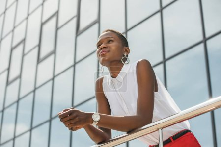 low angle view of stylish attractive african american businesswoman leaning on railing near business center