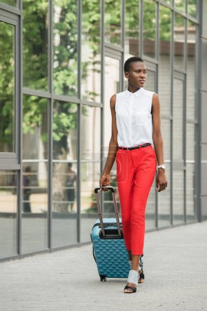 Photo for Stylish attractive african american businesswoman walking with travel bag on street and looking away - Royalty Free Image