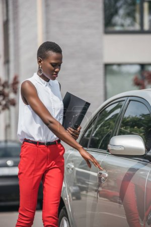 stylish attractive african american businesswoman opening taxi door on street