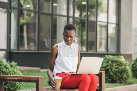 Photo for Stylish attractive african american businesswoman sitting on bench with laptop and coffee to go on street - Royalty Free Image