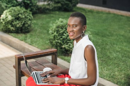 cheerful stylish attractive african american businesswoman using laptop on bench on street