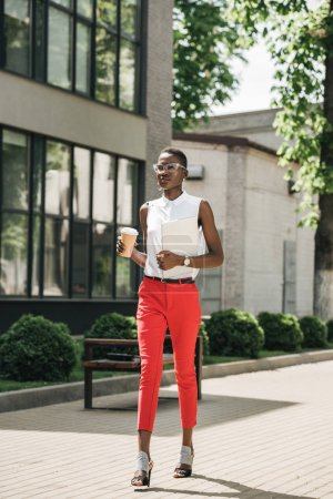 stylish attractive african american businesswoman walking on street with coffee in paper cup and laptop