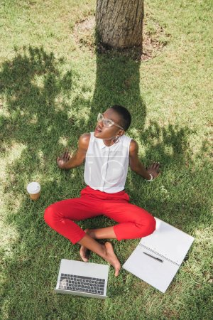 high angle view of stylish attractive african american businesswoman sitting on grass in park and looking up