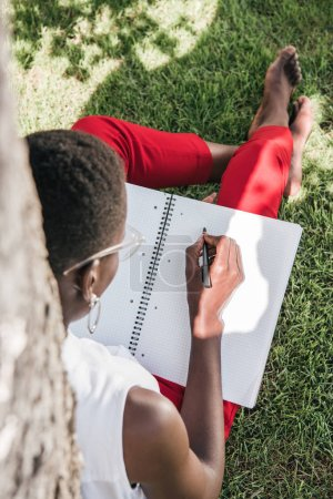 high angle view of fashionable african american businesswoman leaning on tree and writing to notebook in park