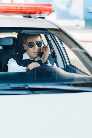middle aged policeman in sunglasses talking on radio set in car