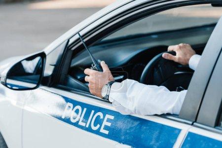 Photo pour Image recadrée d'un policier tenant un talkie-walkie dans une voiture - image libre de droit