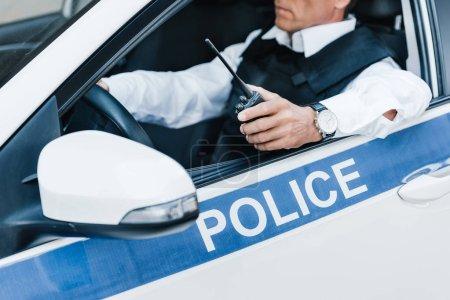 Photo pour Vue partielle du mâle policier en gilet pare-balles maintenant walkie-talkie en voiture - image libre de droit